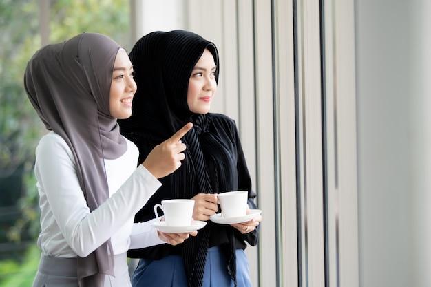 2つのアジアのイスラム教徒の女性に立っていると一杯のコーヒーとオフィスで話しています。現代のイスラム教徒のライフスタイルのコンセプト。
