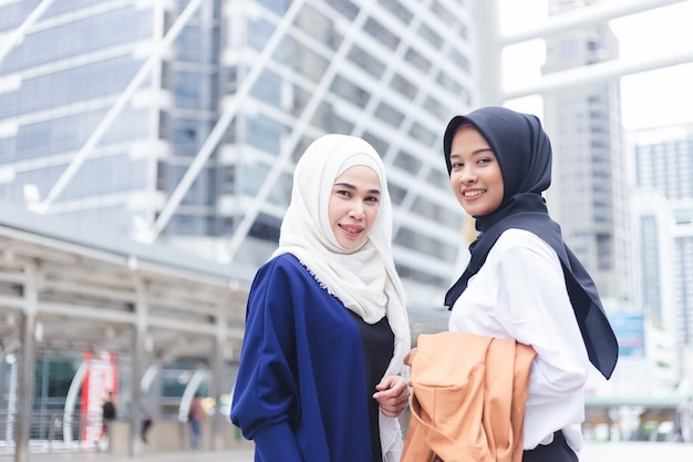 Two asian muslim woman standing and smiling looking camera in city.