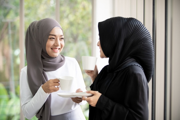 Two asian muslim woman standing and talking in the office with a cup of coffee. modern muslim lifestyle concept.