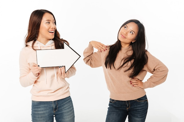Two asian positive ladies sisters holding arrow.