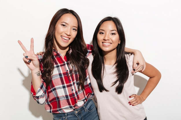 Two asian pretty cheerful ladies sisters showing peace gesture.
