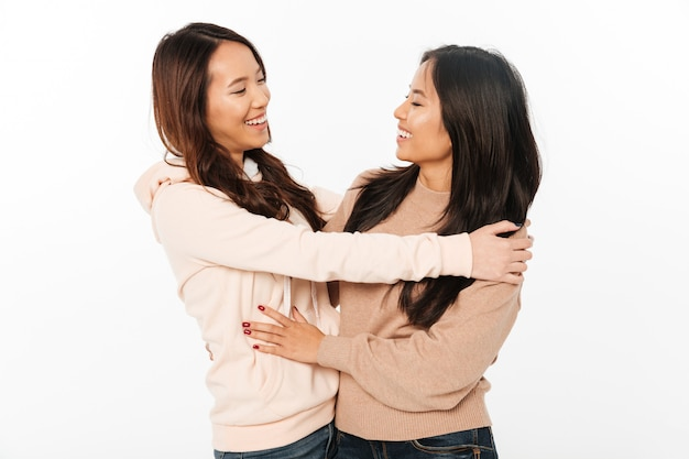 Two asian pretty ladies sisters hugging with each other.