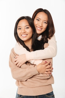 Two asian pretty smiling ladies sisters hugging