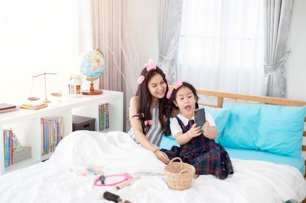 寝室のベッドの上に座って化粧をしている2つのアジアの姉妹。
