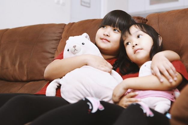 Two asian sisters sitting on couch with doll watching tv at home