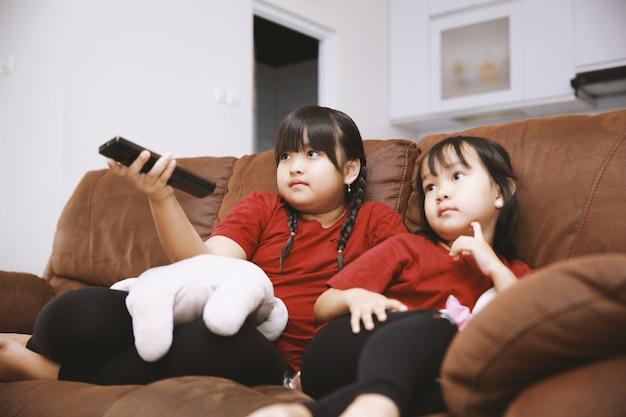 自宅でテレビを見ている人形と一緒にソファに座っている2人のアジアの姉妹