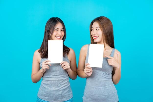 Две азиатские улыбающиеся молодые женщины, показывающие и представляющие плакаты на изолированном синем цветном фоне