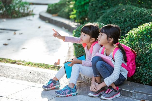 함께 앉아있는 동안 멀리 가리키는 제복을 입은 두 명의 아시아 학생