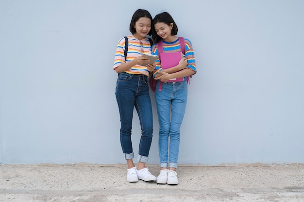 Two asian student young girl looking laptop at school on blue wall