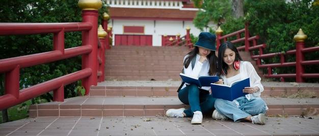 Два азиатских студента читают книгу, сидя на лестнице в университетском городке.