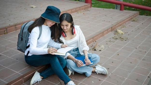 두 명의 아시아 학생이 대학 캠퍼스의 계단에 앉아 메모를 공유하고 있습니다.
