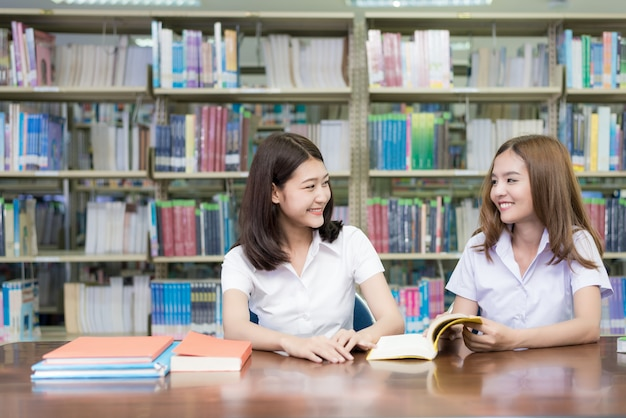 Two asian students studying together in library at university.