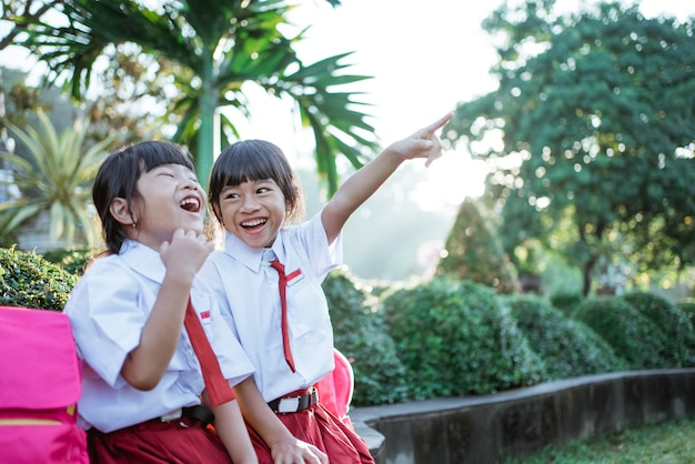 Two asian students in uniform pointing away while sitting togehter