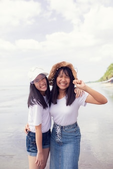 海のビーチで2つのアジアのティーンエイジャーの幸せ
