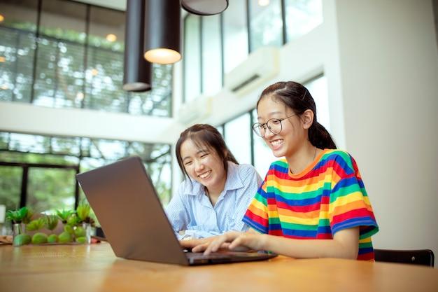 ラップトップコンピューターで作業して2つのアジアのティーンエイジャー