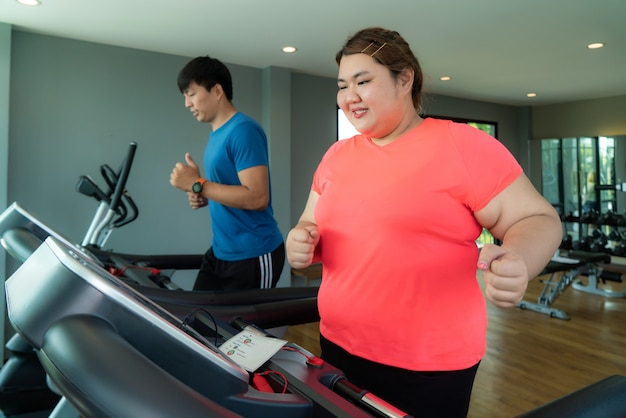 두 아시아 트레이너 남자와 체육관에서 디딜 방아에 훈련을 운동과 체중 여자