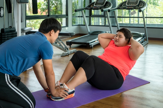 Two asian trainer man and overweight woman exercising sit up together in modern gym, happy and smile during workout. fat women take care of health and want to lose weight concept.
