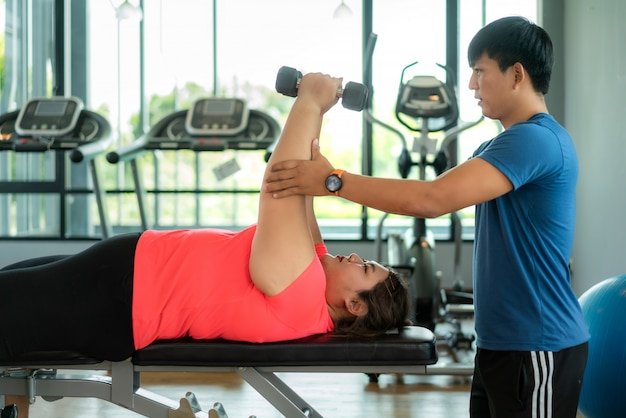 Two asian trainer man and overweight woman exercising with dumbbell together in modern gym, happy and smile during workout. fat women take care of health and want to lose weight concept.