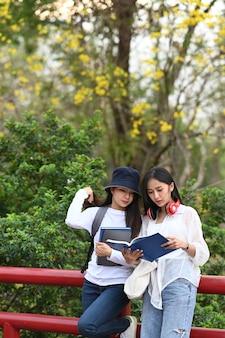 Два азиатских студента университета говорят о результатах экзаменов и стоят вместе в кампусе колледжа
