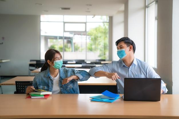 Два азиатских студента университета с маской для лица встречаются и приветствуют друга, касаясь локтя