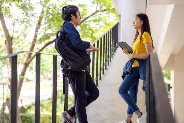 Два азиатских студента университета идут и разговаривают с классом по пешеходной дорожке великолепного здания кампуса.