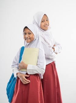 Two asian veiled girls wearing elementary school uniforms stand back to each other while carrying a ...