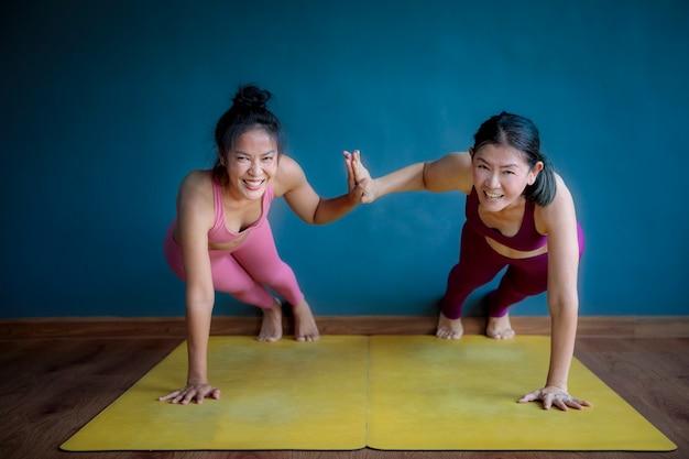 Две азиатские женщины занимаются йогой со счастьем
