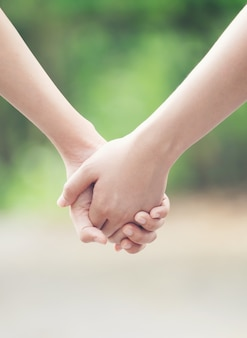 Two asian woman holding hands