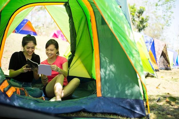 Две азиатские женщины, читающие книгу в палатке кемпинга.