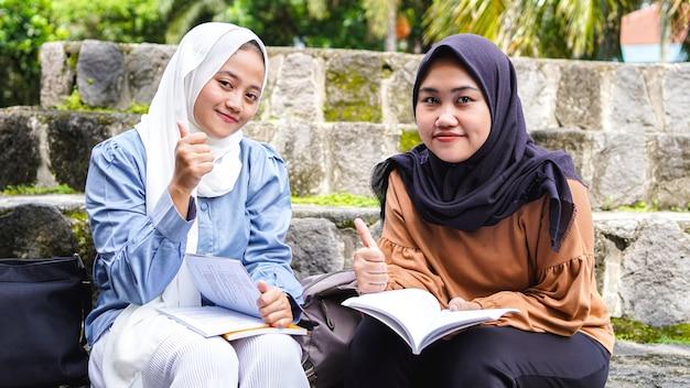 확인 제스처와 함께 논의 두 아시아 여자 학생 친구