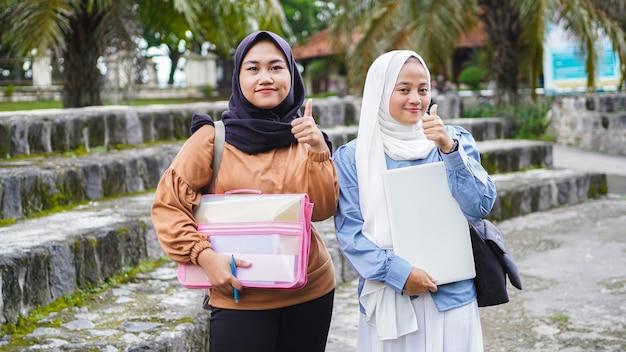 확인 제스처와 함께 캠퍼스에 걸어 두 아시아 여자 학생 친구