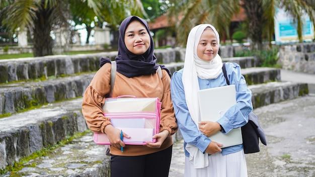 Две азиатские женщины-студенты друг гуляют по кампусу