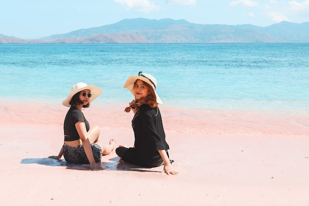 Two asian woman in summer hat sitting and looking to camera in pink sandy beach at labuan bajo