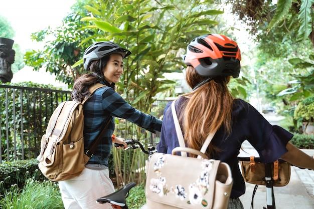 チャットしながら折りたたみ自転車で歩く2つのアジアの女性