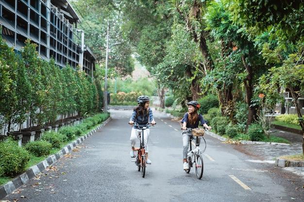 2つのアジアの女性のヘルメットを着用し、バッグを運ぶ自転車に乗る