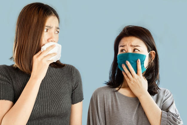 Two asian women afraid of each other from covid-19 virus