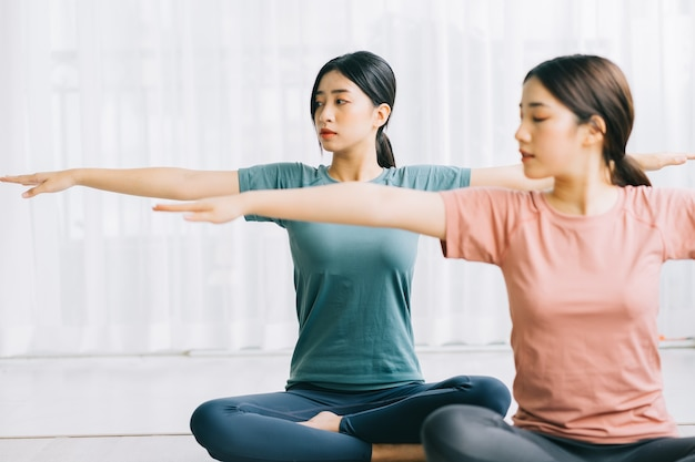 2人のアジア人女性が自宅で瞑想を実践しています