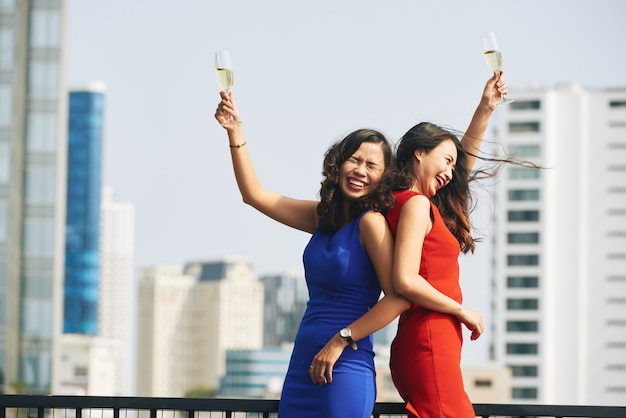 Two asian women in bright dresses holding up champagne flutes at urban rooftop party