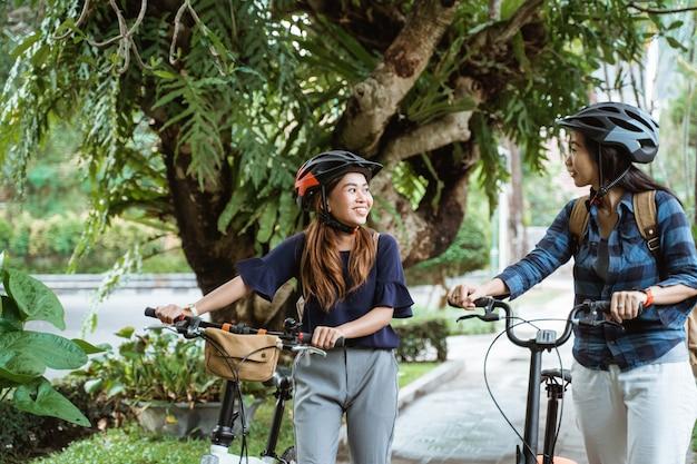 折りたたみ自転車で歩きながらおしゃべりしながら歩く2人のアジア女性