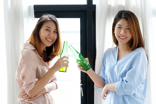Two asian women drinking beer at party