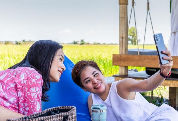 두 명의 아시아 여성 친구 또는 레즈비언 커플이 휴대전화로 셀카를 찍고 있다