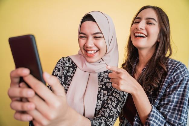 스마트폰을 사용하여 비디오 중에 행복하게 웃고 있는 두 아시아 여성