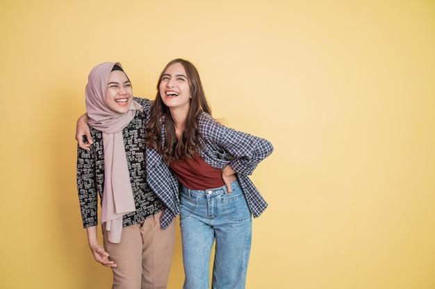 肩に手を当てて抱き合って笑っている2人のアジア人女性