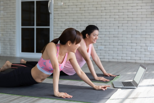 Two asian women looking laptop to learn yoga training from internet