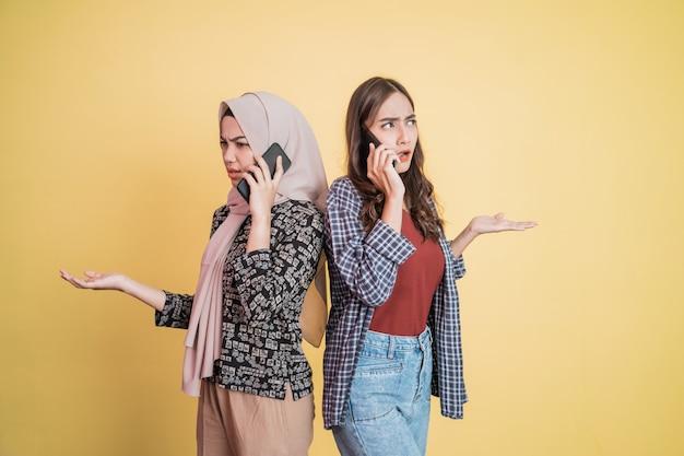 등을 맞대고 서서 전화를 걸고 있는 두 명의 아시아 여성