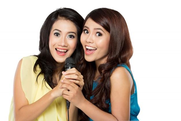 一緒に歌う2人のアジア女性