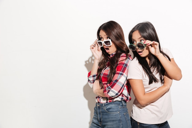 Two asian women sisters wearing sunglasses