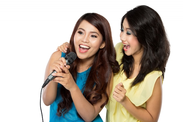 Two asian women in striped t-shirt singing together
