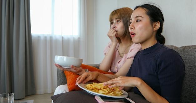 リモコンを使ってテレビを見ている2人のアジア人女性。休暇中に自宅のソファでおやつを食べて笑いを楽しんでいます。