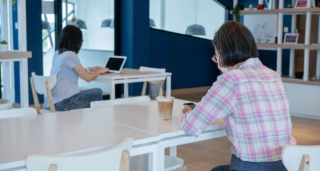 フェイスマスクを着用し、ビデオ通話やビデオ作業にスマートフォンとラップトップを使用している2人のアジア女性が、安全な社会的距離を保つために別のテーブルに座っています。